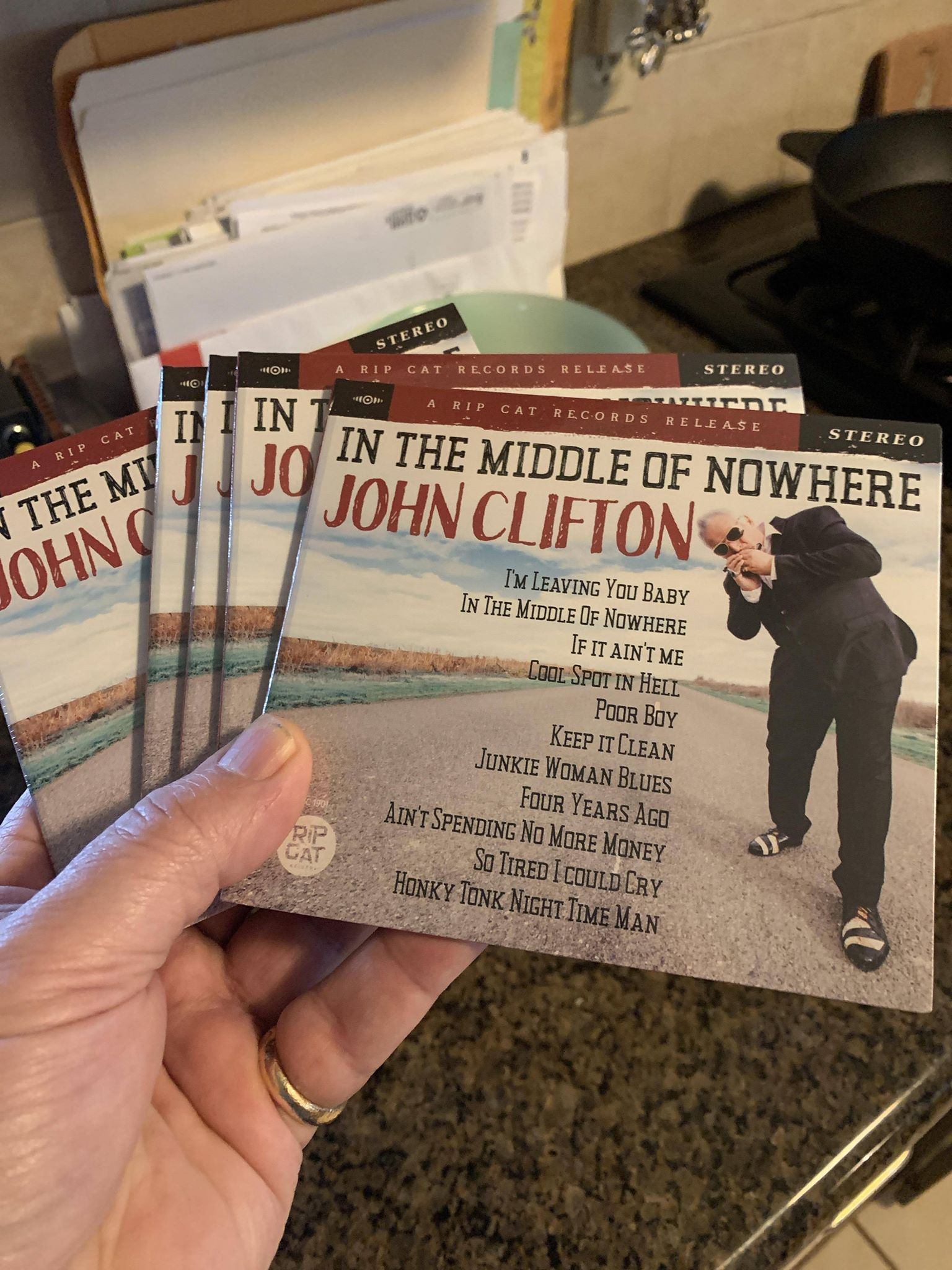 John Clifton's CDs, held in his own hand, Photos & Cover Design by Rick Horowitz Photography